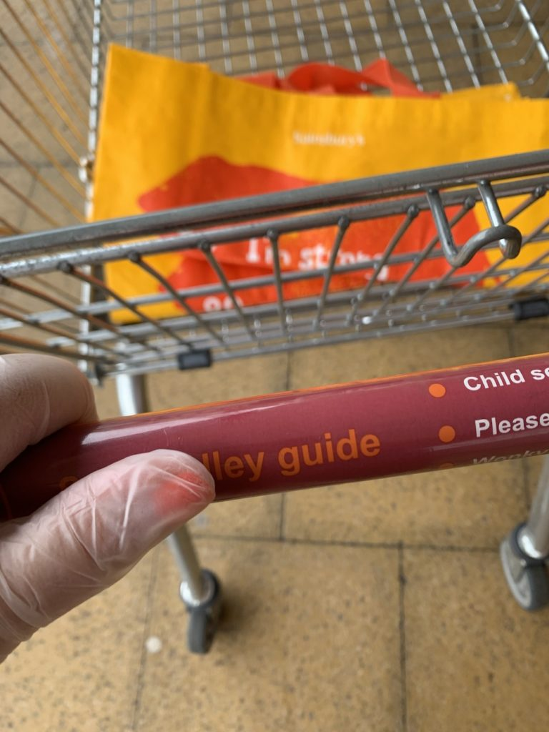 gloved hand pushing supermarket trolly