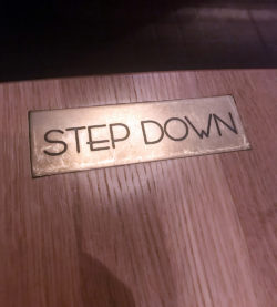 Step Down sign on table