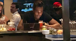 Male at bar looking at phone